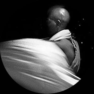 Exu, 2005, da série Heranças compartilhadas. Foto: Denise Camargo Esta imagem, tomada em preto-e-branco, durante um ritual em templo da religião vodu, em Nova Orleans, Estados Unidos, retrata um homem negro, alto, com a cabeça completamente nua e de perfi, vestindo uma espécie de capa que aparece em cor branca e presa, transversalmente, em um dos ombros. O segundo plano, ao fundo, é escuro. Não podemos ver o seu rosto, pois só a parte lateral de seu corpo está iluminada. Ele está incorporado pela divindade Exu e dança. A imagem registra o seu movimento. Segundo a mitologia, Exu tem um temperamento irascível e brincalhão. É o mensageiro que propicia a comunicação entre homens e os outros deuses de origem africana. E deve ser sempre o primeiro a receber oferendas, por isso é colocado à entrada das casas.